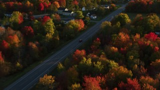 AX149_139 - 6K stock footage aerial video tracking car on road through small town nestled among trees, autumn, Stockton Springs, Maine, sunset