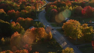 AX149_141 - 6K stock footage aerial video tracking car on road through quaint town, autumn, Stockton Springs, Maine, sunset