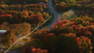 AX149_142 - 6K stock footage aerial video tracking a car moving through smalll town, autumn, Stockton Springs, Maine, sunset