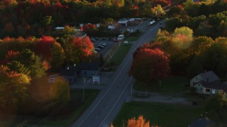 AX149_143 - 6K stock footage aerial video tracking car on road through small town, autumn, Stockton Springs, Maine, sunset