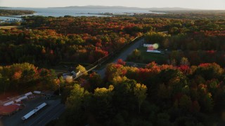 AX149_144 - 6K stock footage aerial video tracking a car on road passing by small town, autumn, Stockton Springs, Maine, sunset
