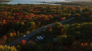 AX149_145 - 6K stock footage aerial video tracking car on road passing through small town, and trees, autumn, Stockton Springs, Maine, sunset