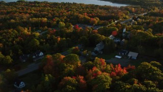 AX149_146 - 6K stock footage aerial video flying away from small town and trees, autumn, Stockton Springs, Maine, sunset
