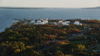 AX149_147 - 6K stock footage aerial video flying by waterfront oil refinery and gas company, autumn, Searsport, Maine, sunset