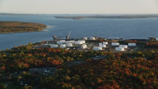 AX149_148 - 6K stock footage aerial video flying by oil refinery and gas company along the water, autumn, Searsport, Maine, sunset