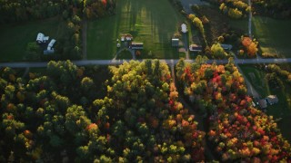 AX149_150 - 6K stock footage aerial video of a bird's eye view over rural homes, forest in autumn, Searsport, Maine, sunset