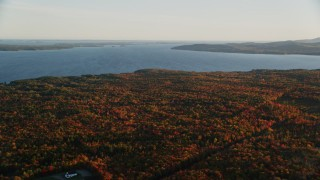 AX149_151 - 6K stock footage aerial video flying by Belfast Bay, colorful forest in autumn, Searsport, Maine, sunset