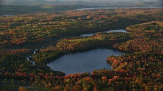 AX149_152 - 6K stock footage aerial video flying by McClure Pond, Cain Pond, forest in autumn, Searsport, Maine, sunset
