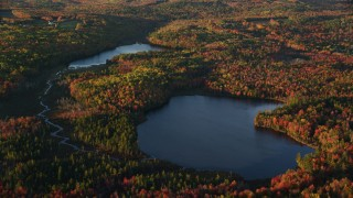 AX149_153 - 6K stock footage aerial video flying by ponds among colorful forest in autumn, Searsport, Maine, sunset