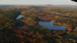 AX149_154 - 6K stock footage aerial video flying by ponds surrounded by forest in autumn, Searsport, Maine, sunset