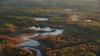 AX149_156 - 6K stock footage aerial video flying high over a pond and colorful forest in autumn, Belfast, Maine, sunset