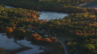AX149_157 - 6K stock footage aerial video flying by ponds surrounded by forest in autumn, Belfast, Maine, sunset