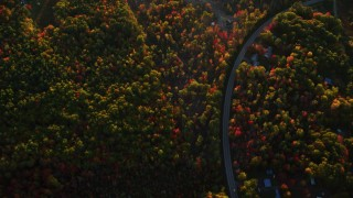 AX149_165 - 6K stock footage aerial video of a bird's eye view over forest and rural homes in autumn, Belfast, Maine, sunset
