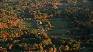 AX149_166 - 6K stock footage aerial video flying by a forest and rural homes, Poors Mill Road, autumn, Belfast, Maine, sunset