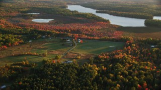 AX149_169 - 6K stock footage aerial video flying by a colorful forest in autumn and rural homes, Belmont, Maine, sunset