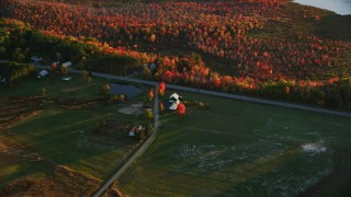 AX149_170 - 6K stock footage aerial video approaching a rural home near Route 3, forest in autumn, Belmont, Maine, sunset