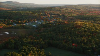 AX149_174 - 6K stock footage aerial video approaching small rural town, colorful trees in autumn, Searsmont, Maine, sunset
