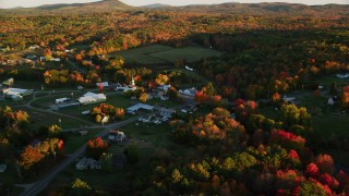 AX149_177 - 6K stock footage aerial video orbiting small rural town near colorful forest, autumn, Searsmont, Maine, sunset