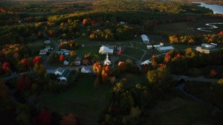 AX149_179 - 6K stock footage aerial video orbiting a small rural town, colorful trees in autumn, Searsmont, Maine, sunset