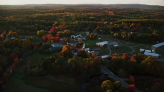 AX149_180 - 6K stock footage aerial video orbiting a small rural town and trees in autumn, Searsmont, Maine, sunset