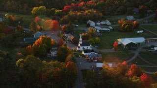 AX149_181 - 6K stock footage aerial video orbiting small rural town, church, autumn, Searsmont, Maine, sunset