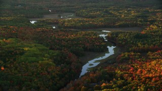 AX149_189 - 6K stock footage aerial video flying by river through a colorful forest in autumn, Liberty, Maine, sunset