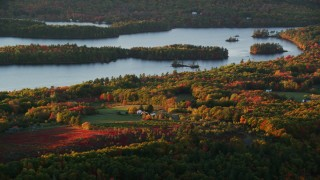 AX149_191 - 6K stock footage aerial video flying by rural homes, Saint George Lake, autumn, Liberty, Maine, sunset