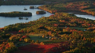AX149_192 - 6K stock footage aerial video flying by Saint George Lake, rural homes, forest in autumn, Liberty, Maine, sunset