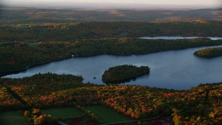 AX149_193 - 6K stock footage aerial video flying by small forested islands, Saint George Lake, autumn, Liberty, Maine, sunset