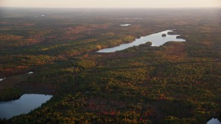 AX149_201 - 6K stock footage aerial video flying by colorful forest, James Pond, Long Pond, autumn, Palermo, Maine, sunset