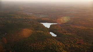 AX149_202 - 6K stock footage aerial video flying by colorful forest, Savade Pond, Fox Pond, autumn, Windsor, Maine, sunset