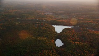 AX149_203 - 6K stock footage aerial video flying by Savade Pond, Fox Pond, dense forrest, autumn, Windsor, Maine, sunset