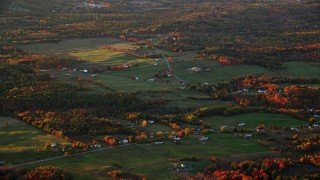 AX149_204 - 6K stock footage aerial video flying by small farms, colorful trees in autumn, Windsor, Maine, sunset