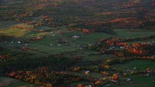AX149_205 - 6K stock footage aerial video flying by colorful trees and small farms at sunset, Windsor, Maine, sunset