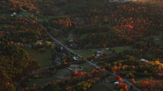 AX149_206 - 6K stock footage aerial video flying by rural homes, Ridge Road, colorful trees in autumn, Windsor, Maine, sunset