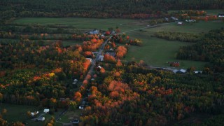 AX149_207 - 6K stock footage aerial video flying by rural homes near Ridge Road, autumn, Windsor, Maine, sunset