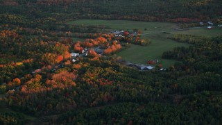 AX149_208 - 6K stock footage aerial video flying by rural homes, colorful trees in autumn, Windsor, Maine, sunset