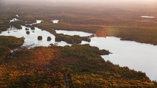AX149_209 - 6K stock footage aerial video flying by Togus Pond, dense colorful forest, autumn, Augusta, Maine, sunset