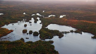 AX149_210 - 6K stock footage aerial video flying by Togus Pond, colorful foliage, autumn, Augusta, Maine, sunset