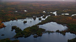 AX149_211 - 6K stock footage aerial video flying by colorful trees in and out of Togus Pond, autumn, Augusta, Maine, sunset
