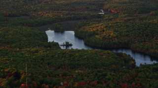AX149_212 - 6K stock footage aerial video flying by colorful foliage, Tolman Pond, autumn, Augusta, Maine, sunset