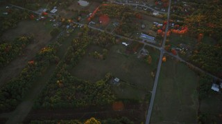AX149_213 - 6K stock footage aerial video of a bird's eye view over rural homes and intersection, autumn, Augusta, Maine, sunset
