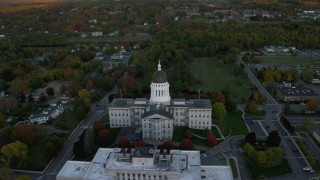 AX149_217 - 6K stock footage aerial video orbiting colorful trees, Maine State House, autumn, Augusta, Maine, twilight