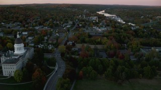 AX149_219 - 6K stock footage aerial video flying by downtown, Kennebec River, autumn, Augusta, Maine, twilight