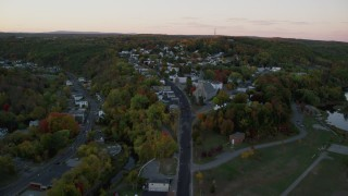 AX149_223 - 6K stock footage aerial video approaching Saint Augustine Catholic Church, autumn, Augusta, Maine, twilight