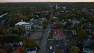 AX149_224 - 6K stock footage aerial video flying over downtown in autumn, approach Lithgow Public Library, Augusta, Maine, twilight