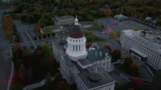 AX149_227 - 6K stock footage aerial video approaching and flying by Maine State House in autumn,  Augusta, Maine, twilight