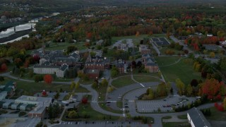 AX149_230 - 6K stock footage aerial video orbiting Maine government offices, colorful trees, autumn, Augusta, Maine, twilight