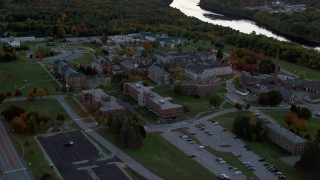 AX149_233 - 6K stock footage aerial video orbiting Maine government offices, river, autumn, Augusta, Maine, twilight