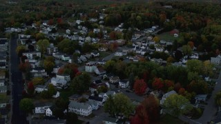 AX149_238 - 6K stock footage aerial video flying over neighborhood  and colorful foliage in autumn, Augusta, Maine, twilight